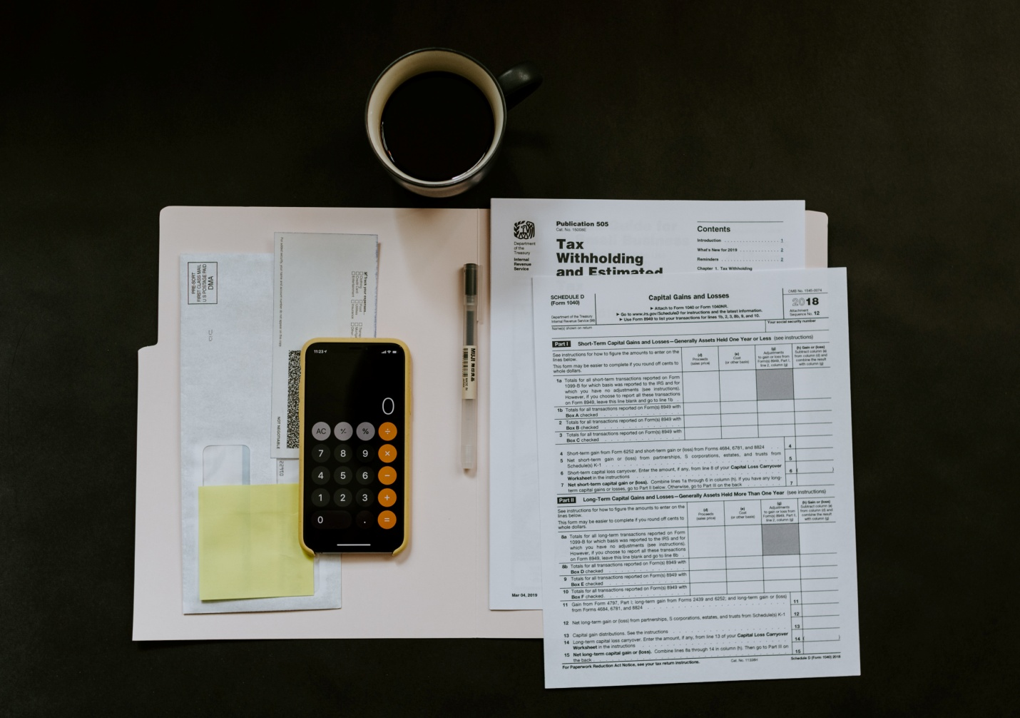 smartphone near ballpoint pen, tax withholding certificate on top of white folder