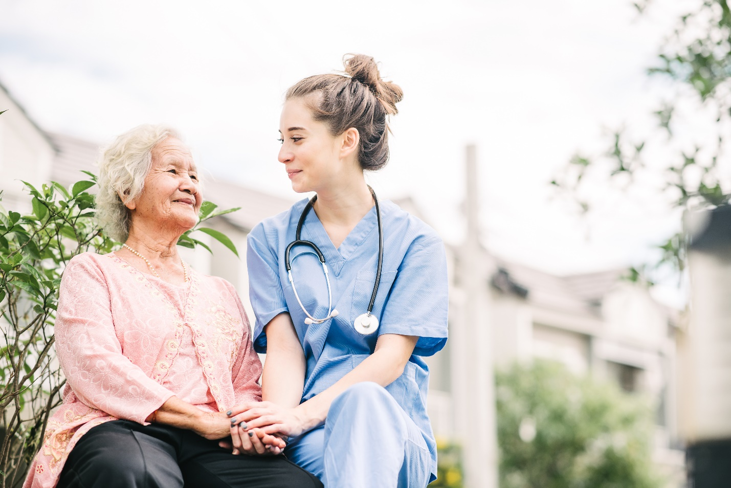 Smiling nurse caregiver holding hand of happy elderly woman outdoor in the park