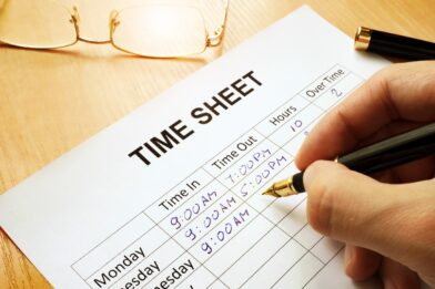 Records work hours in a time sheet.