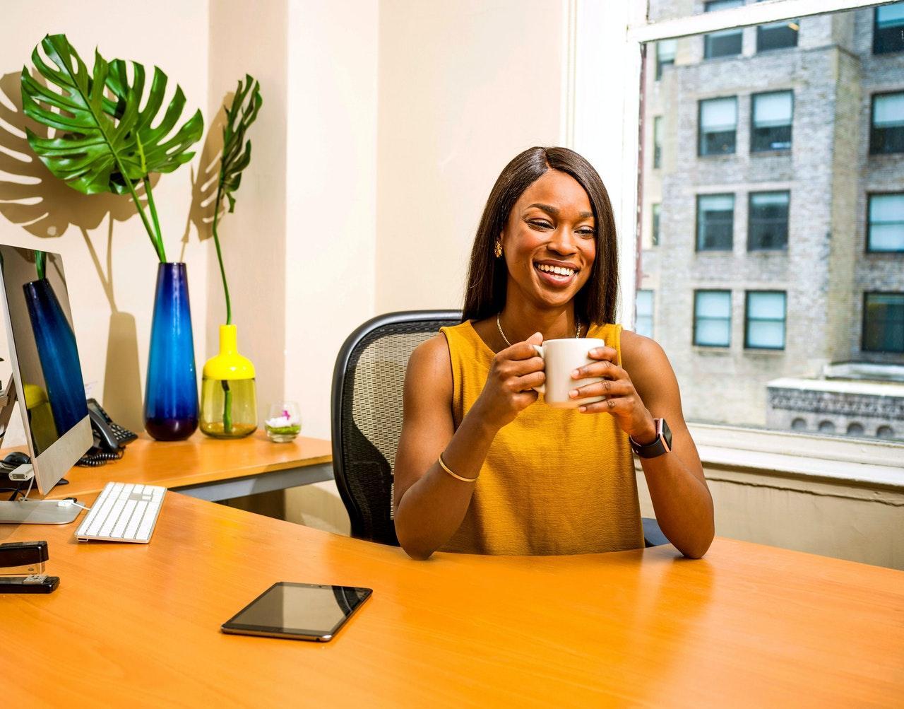 Woman Holding White Ceramic Mug At Desk