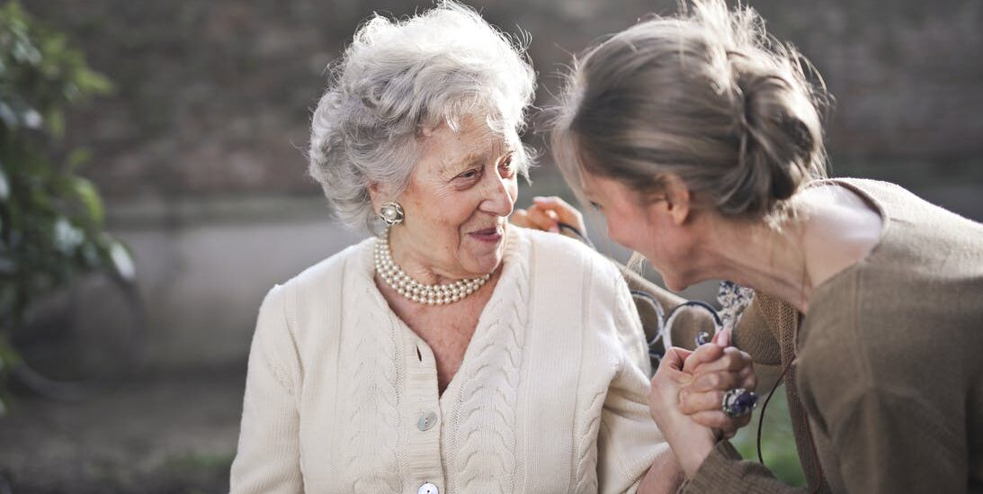 Elderly lady and a pretty young woman holding each other's hands