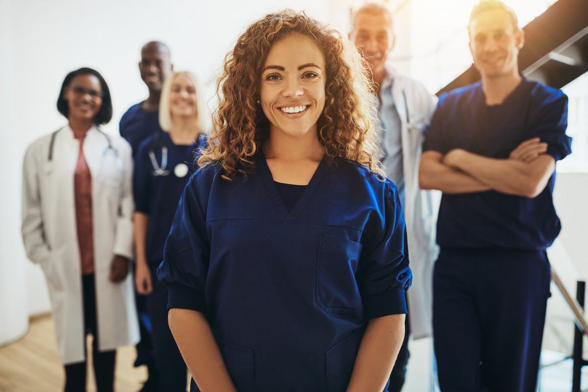 Smiling female doctor standing in a hospital corridor with a group of medical staff