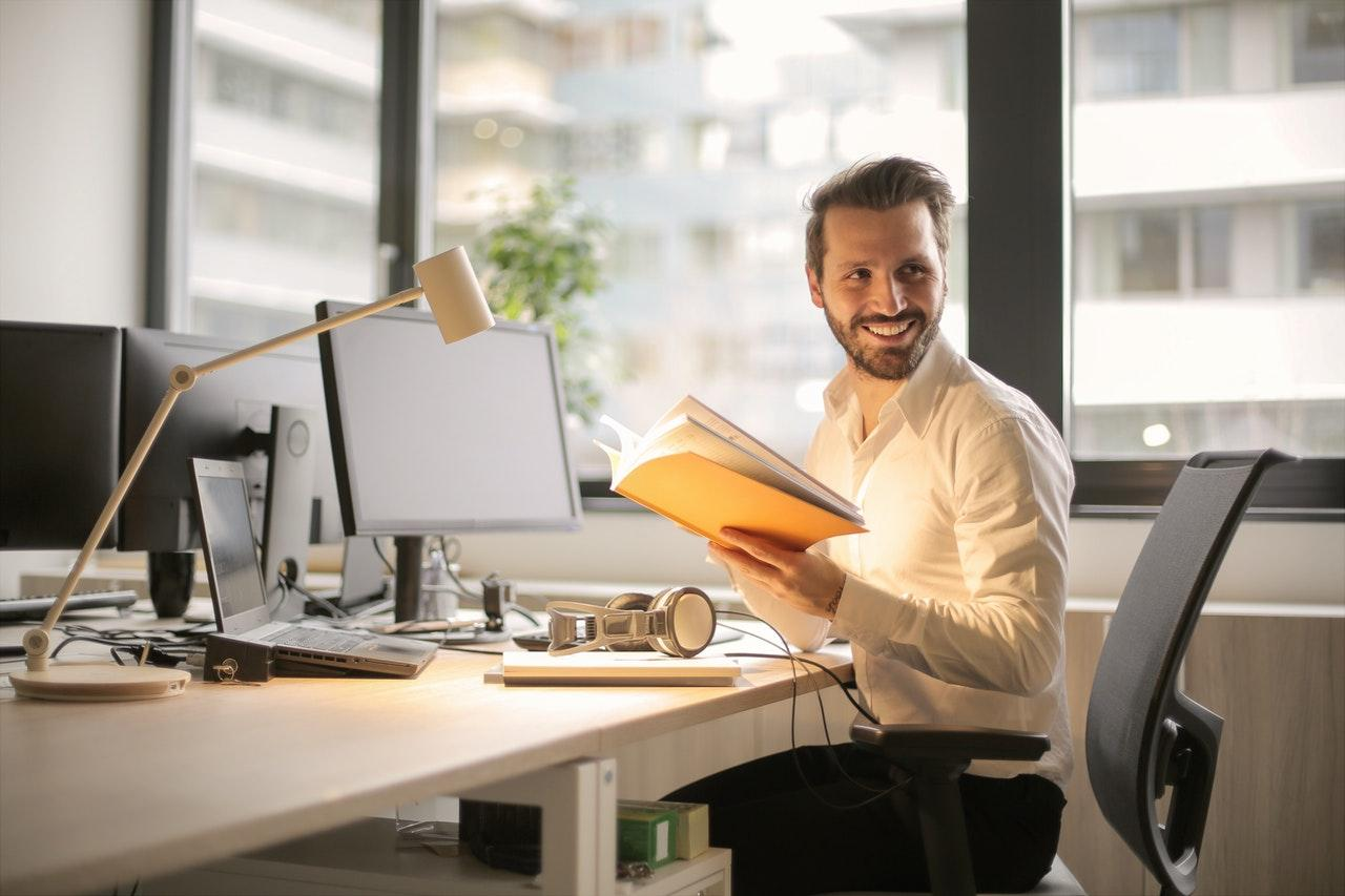 Smiling man sitting at a desk while holding a book