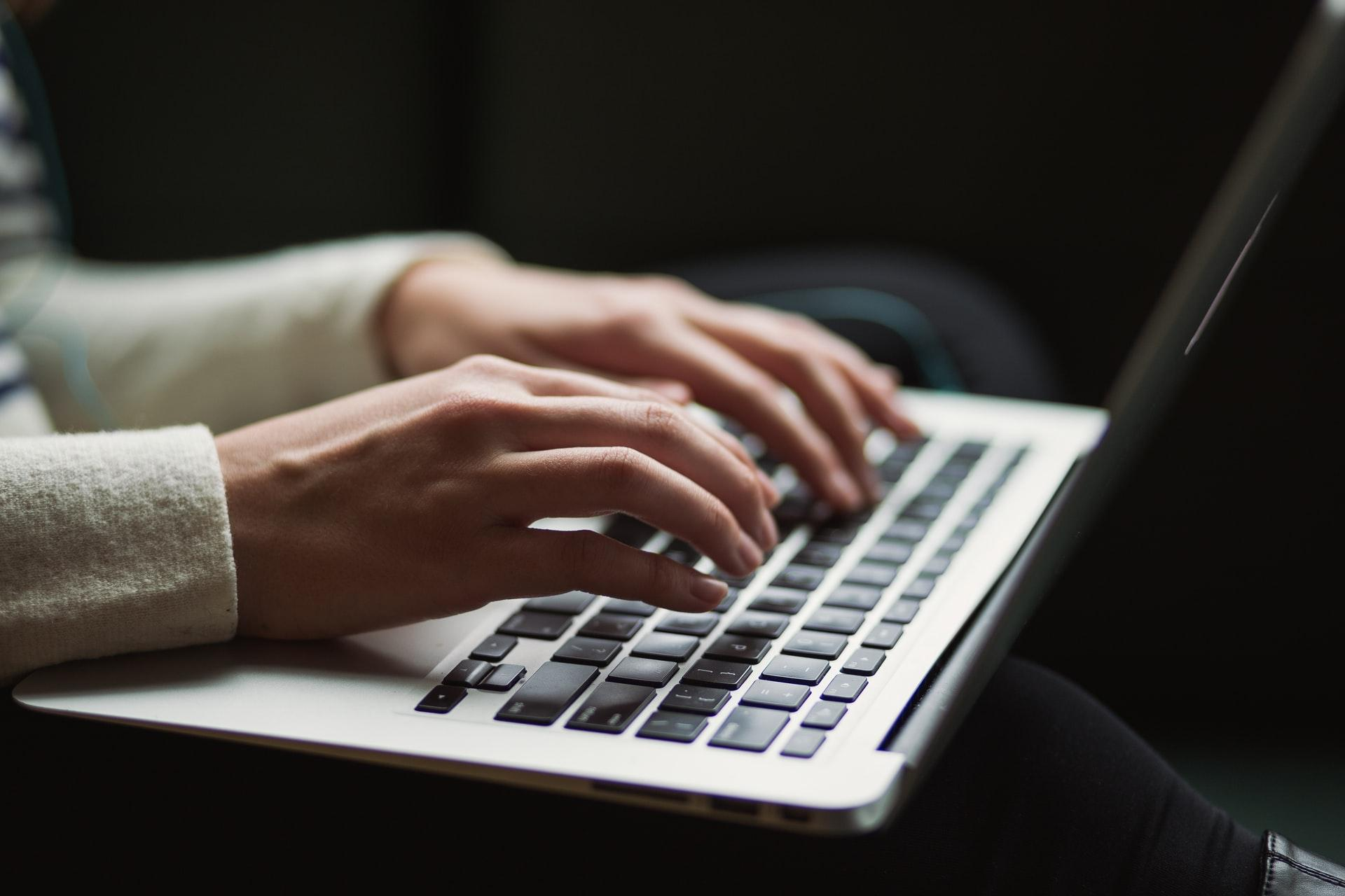 Close-up of woman's hand using laptop